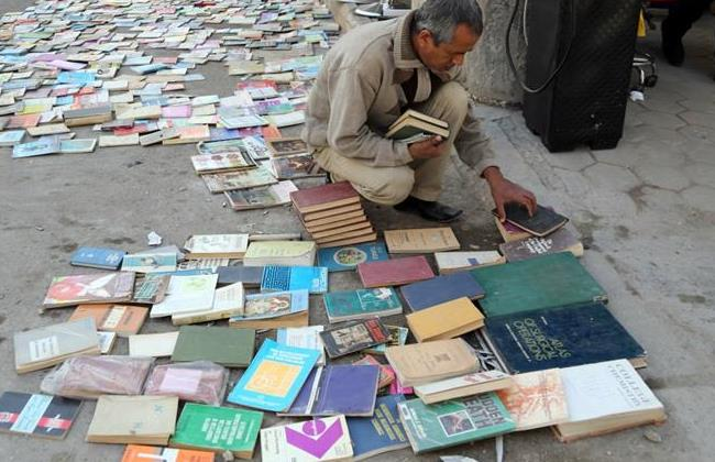 An Iraqi man looks at books on al-Mutanabi Street, home to the city's book market in central Baghdad. (AP Photo/Karim Kadim)