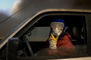 Wearing a mask and glasses against the smoke, dairy farmer Berglind Hilmarsdottir from Nupur looks for cattle lost in the ash clouds. ( AP Photo/Brynjar Gauti )